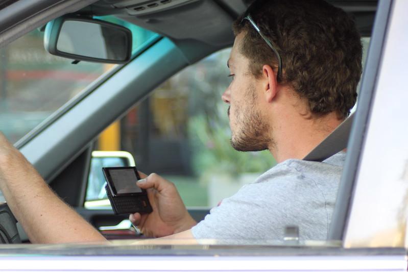 Un homme utilise son téléphone au volant