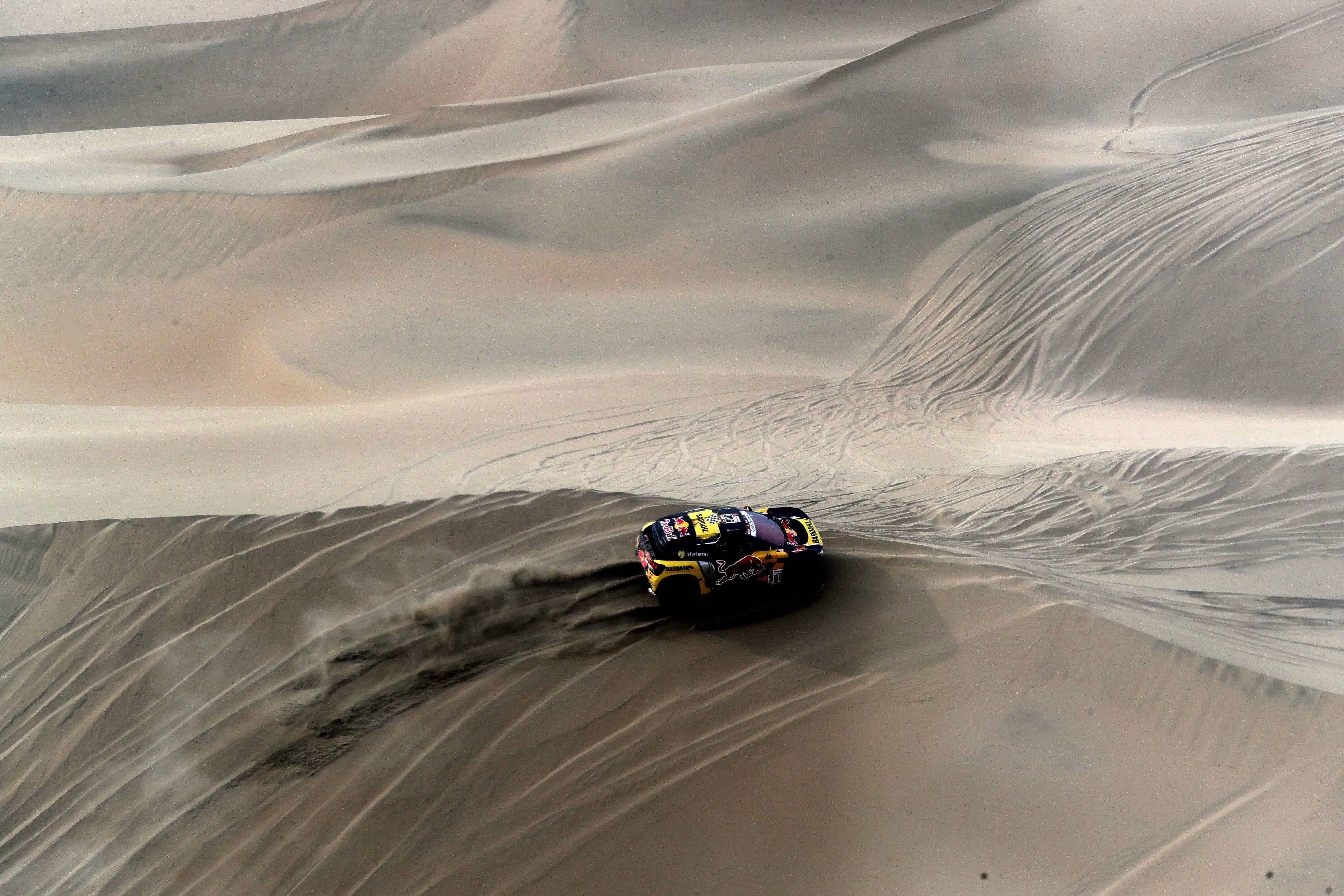 Un chariot monte avec un nuage de poussière sur une dune dans le désert pendant le rallye Dakar.