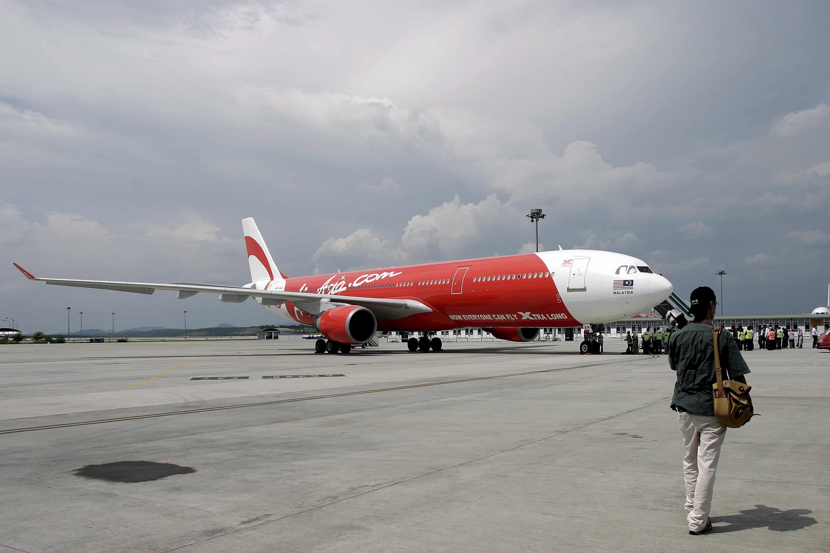 Een man loopt naar een vliegtuig van AirAsia X.