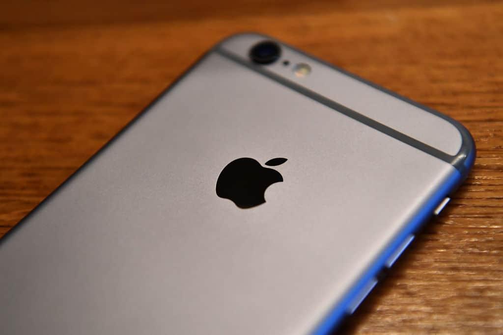 Een grijze iPhone ligt met zijn rug naar boven op een houten tafel.
