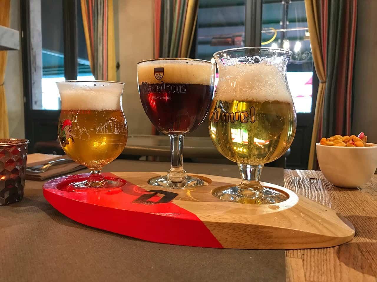 Chouffe, Maredsous en Duvel, drie glazen met Belgisch bier naast elkaar op een houten plank.