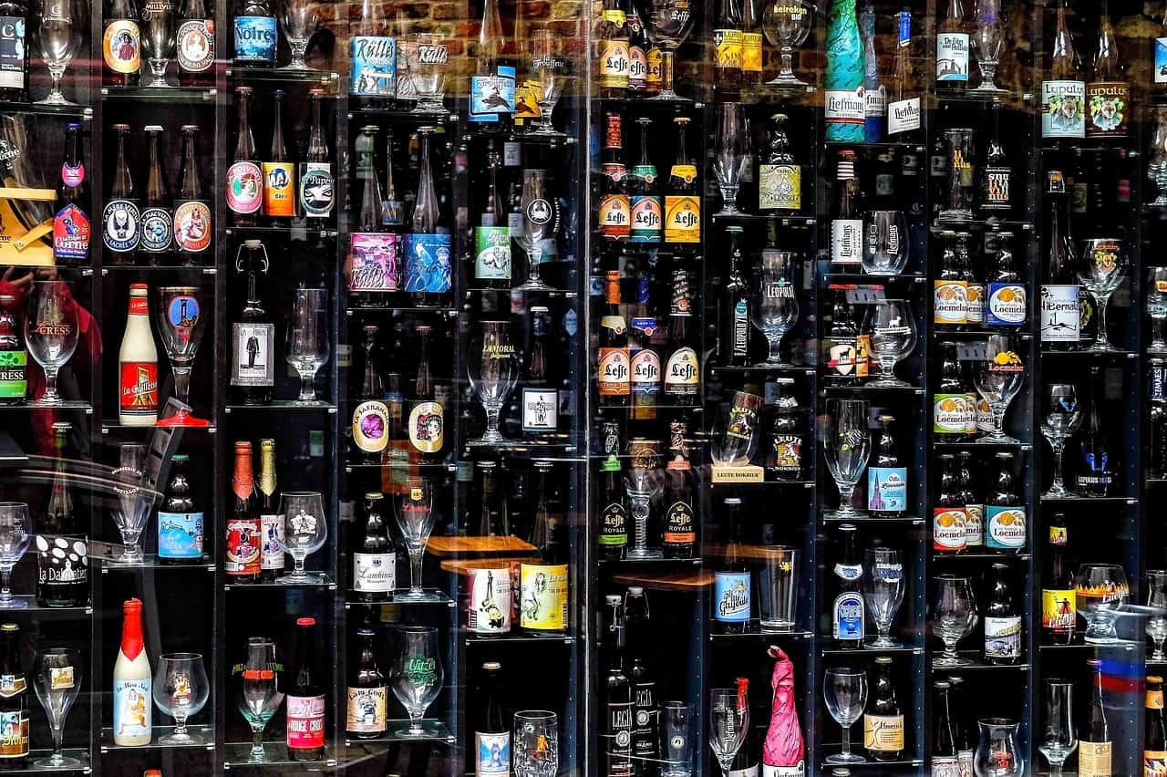 Een grote hoeveelheid flesjes Belgisch bier op een rek.