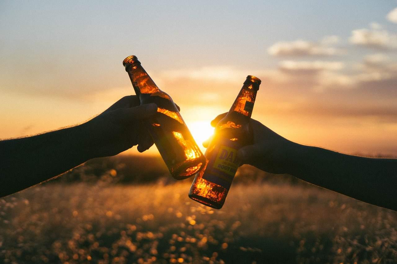 Twee flesjes bier klinken tegen elkaar met de ondergaande zon op de achtergrond.