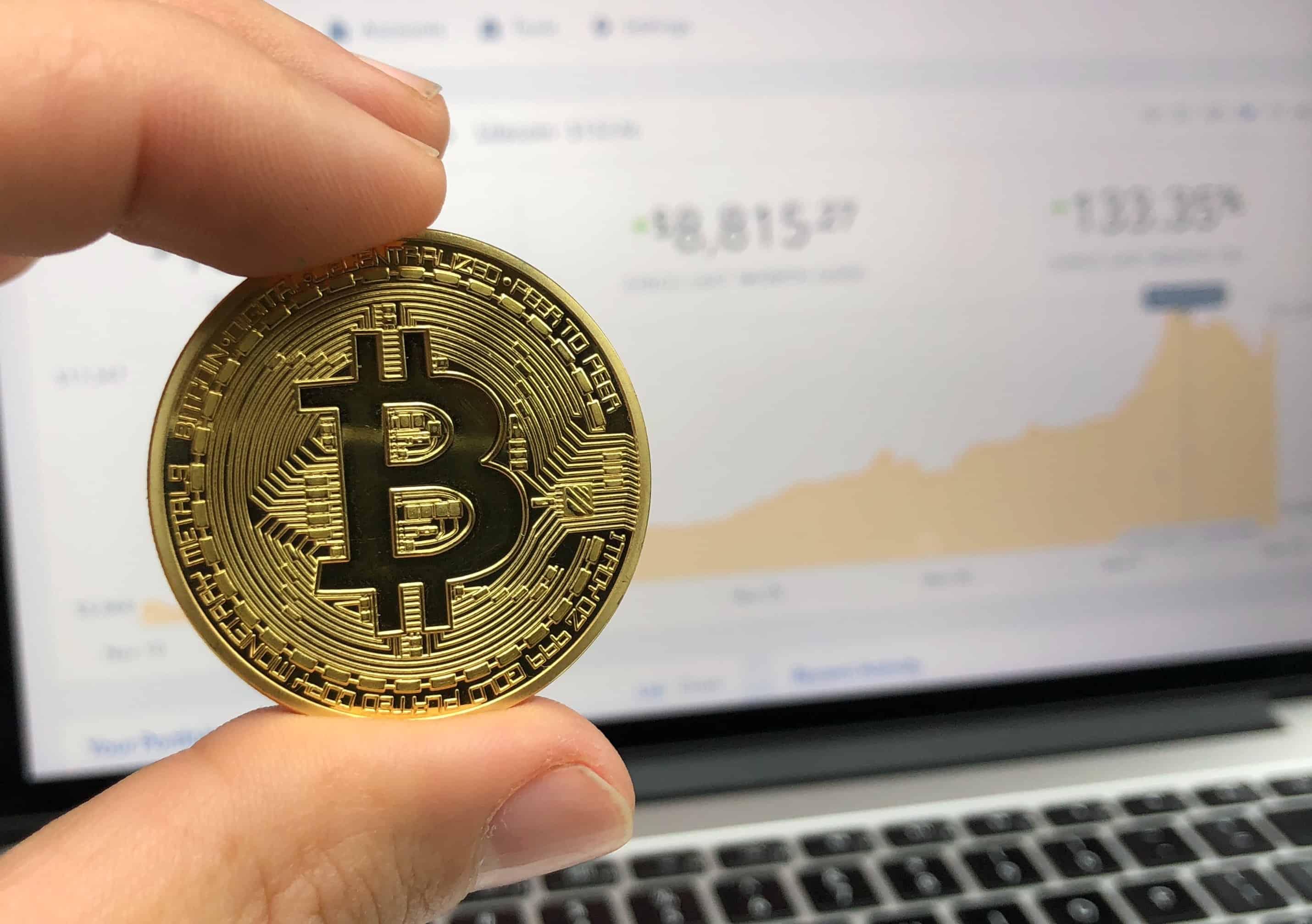 Een hand houdt een muntstuk met een 'B', verwijzend naar Bitcoin, tussen wijsvinger en duim met op de achtergrond het scherm van een pc waarop beurskoersen zijn afgebeeld.