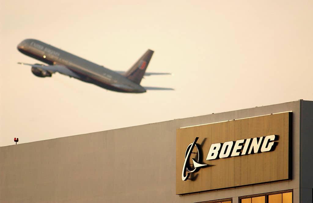 Een vliegtuig stijgt op boven het gebouwen met het logo van Boeing.