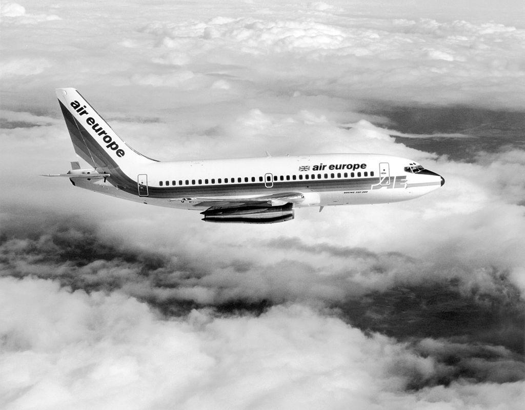 Un avion du modèle Boeing 737 vole au-dessus du nuage sur une image en noir et blanc.