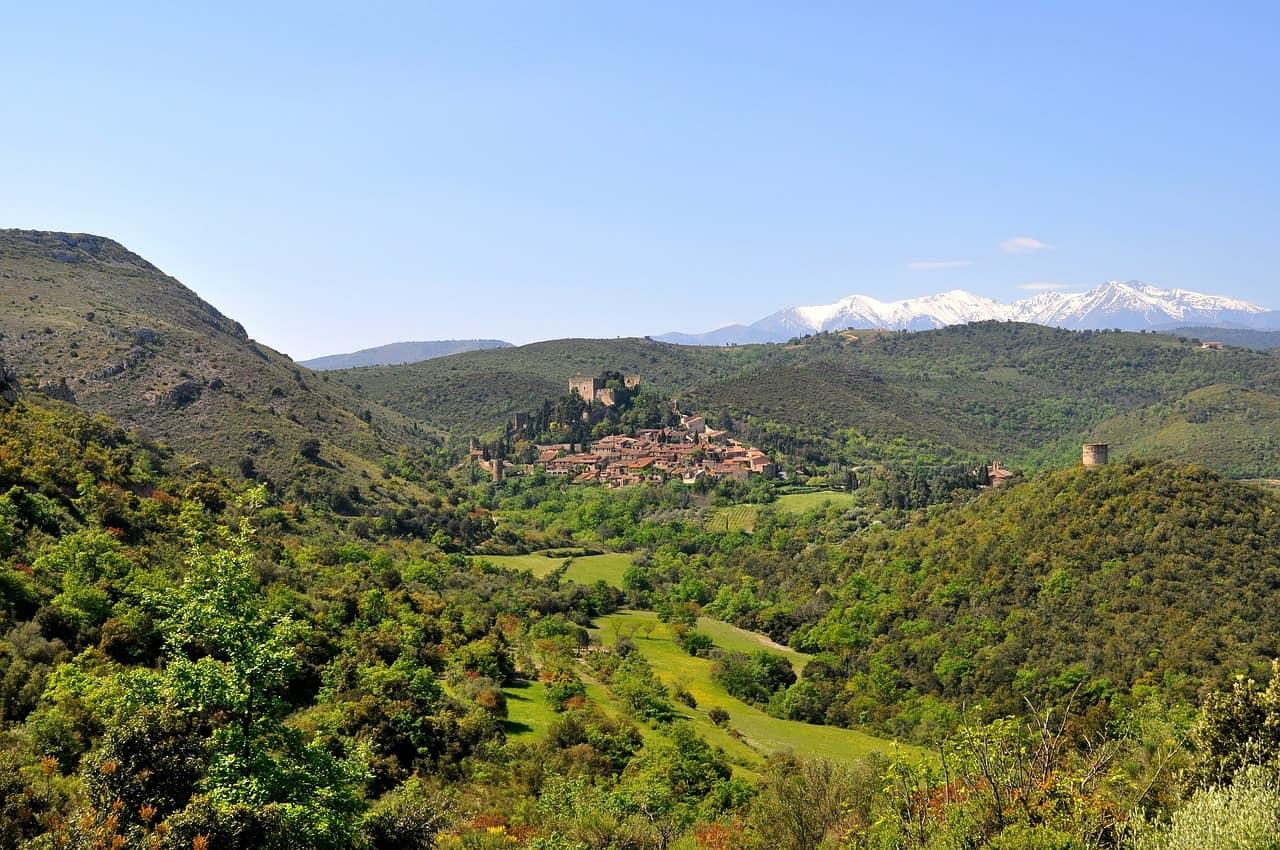 Een groen landschap met in de verte Castelnou, een van de mooiste Franse dorpjes.