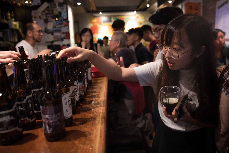 Une Chinoise à lunettes regarde une bouteille de bière sur le comptoir.