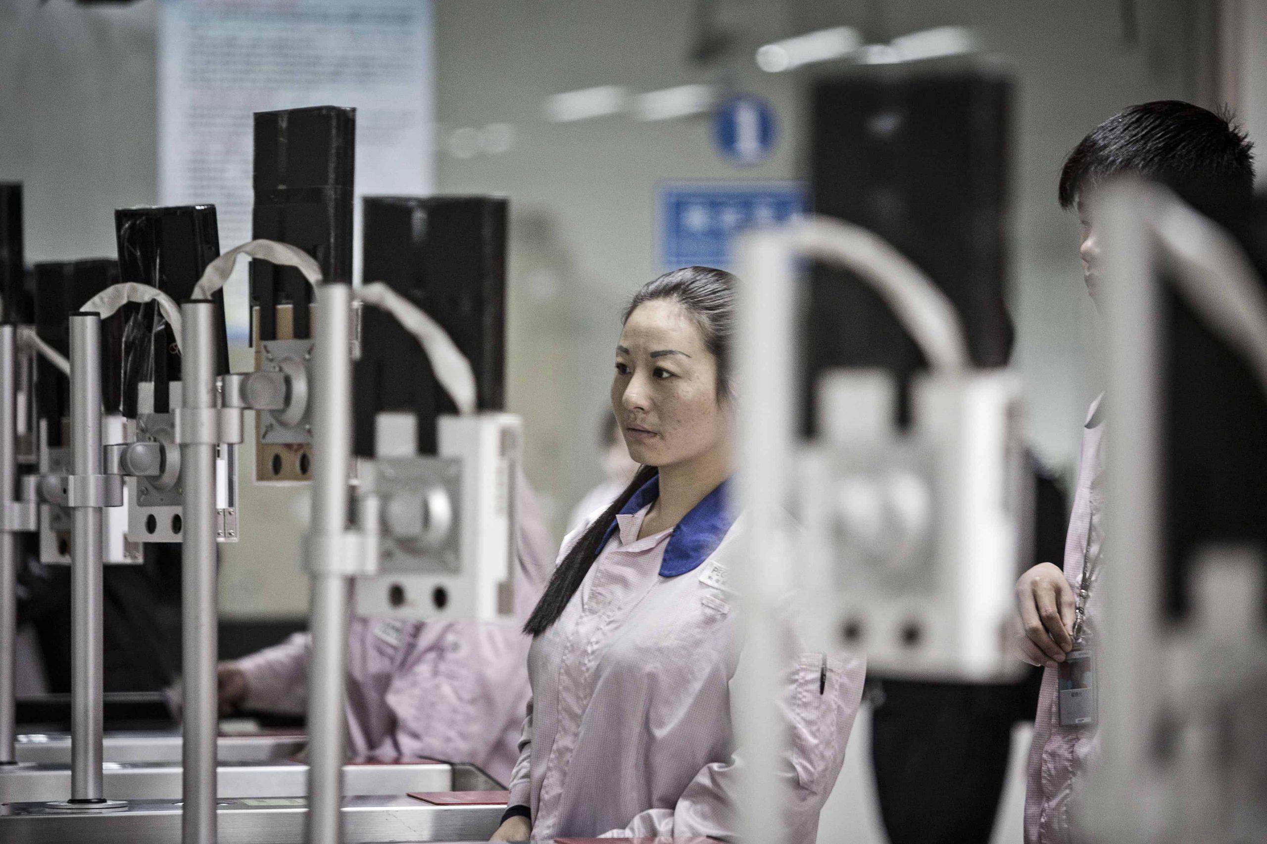 Des Chinoises franchissent un portique équipé de technologie de reconnaissance faciale à l'entrée d'une usine