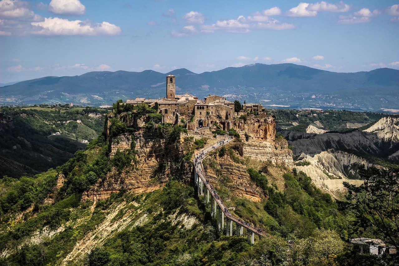 Un village avec un clocher surplombe un paysage de montagne.  Civita di Bagnoregio est l