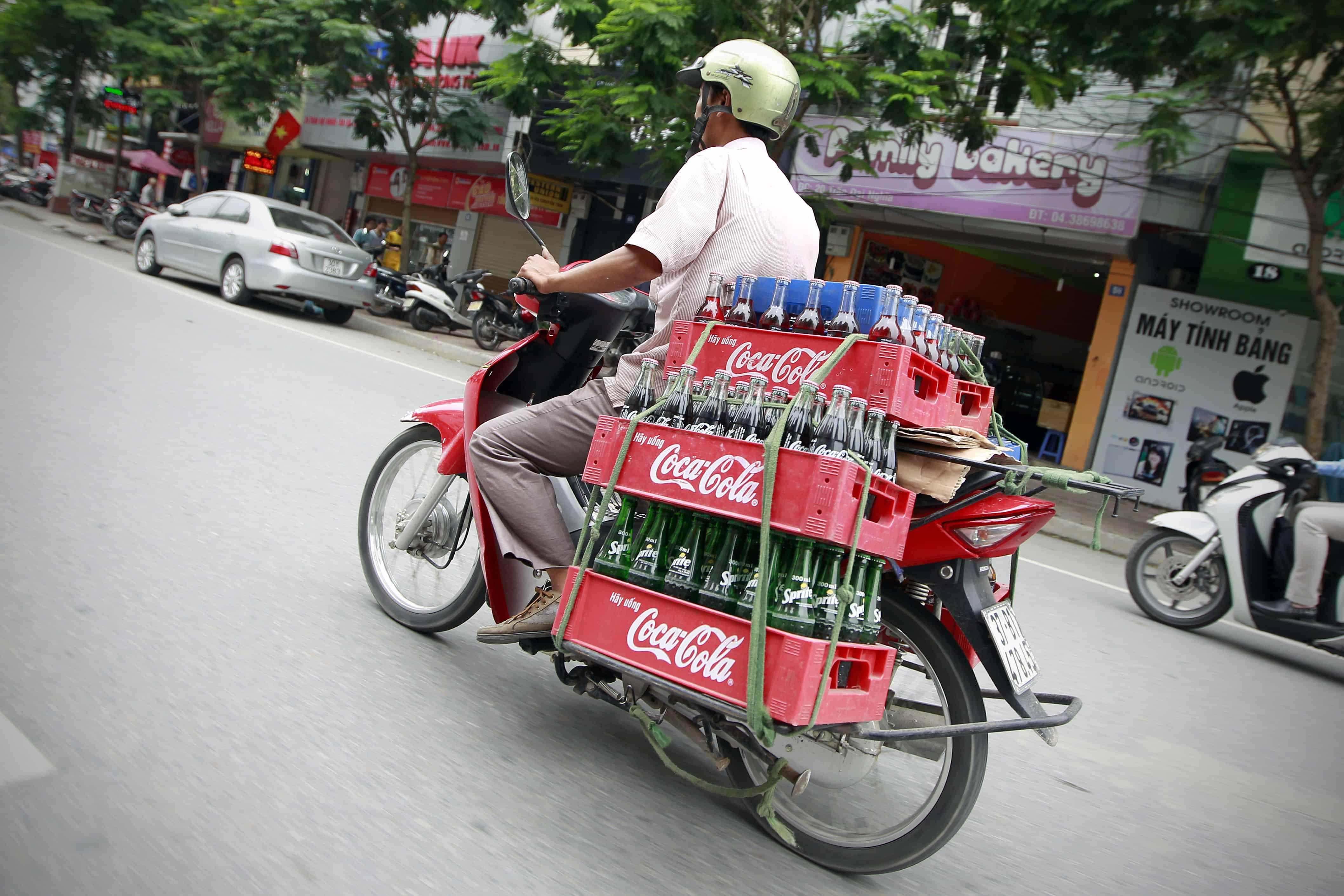 Un scooter chargé de Coca-Cola roule dans une rue du Vietnam.