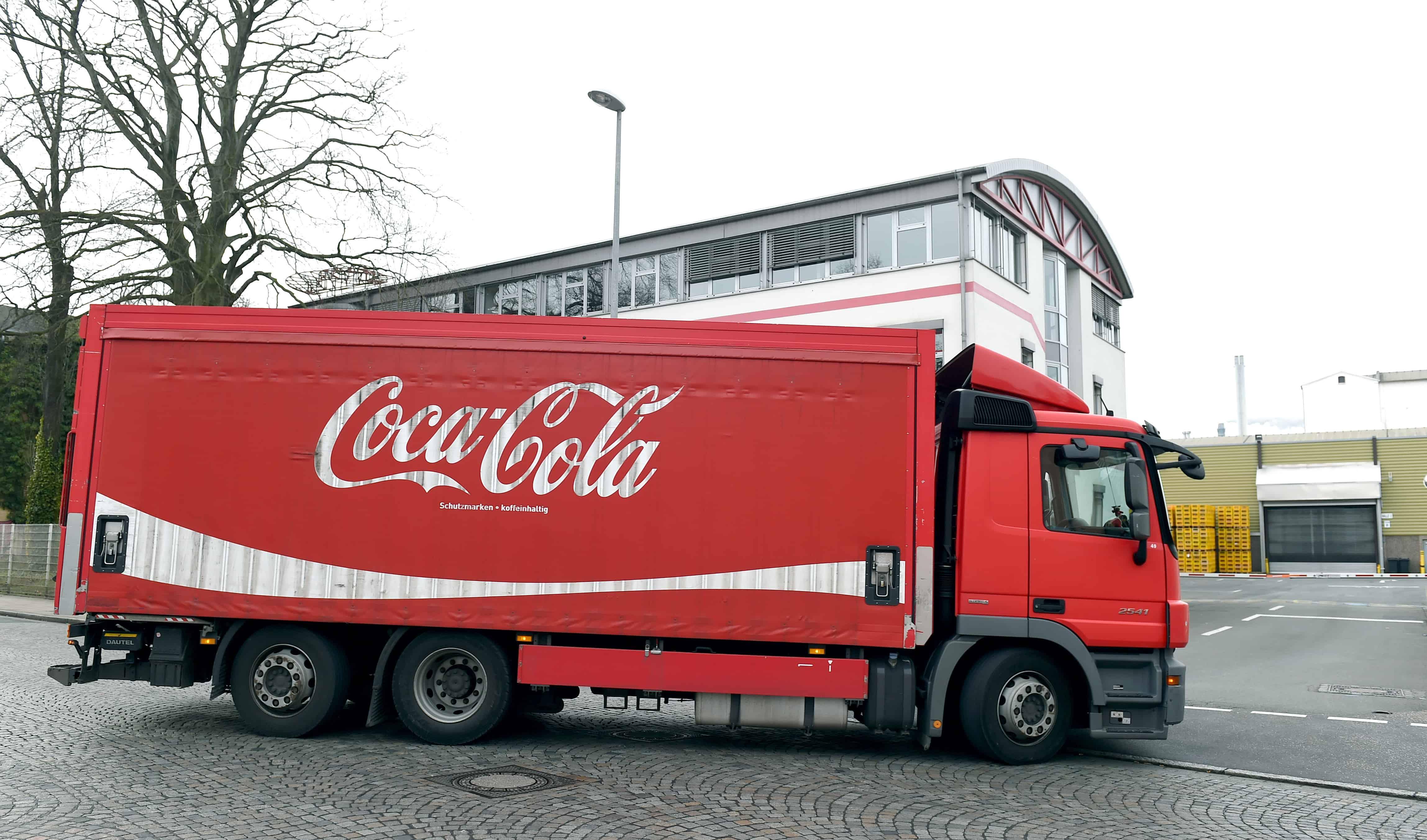 Un camion rouge Coca-Cola passe sur la piste.