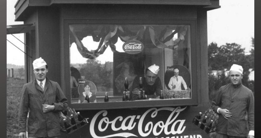 Les hommes posent dans un kiosque qui vend du Coca-Cola.