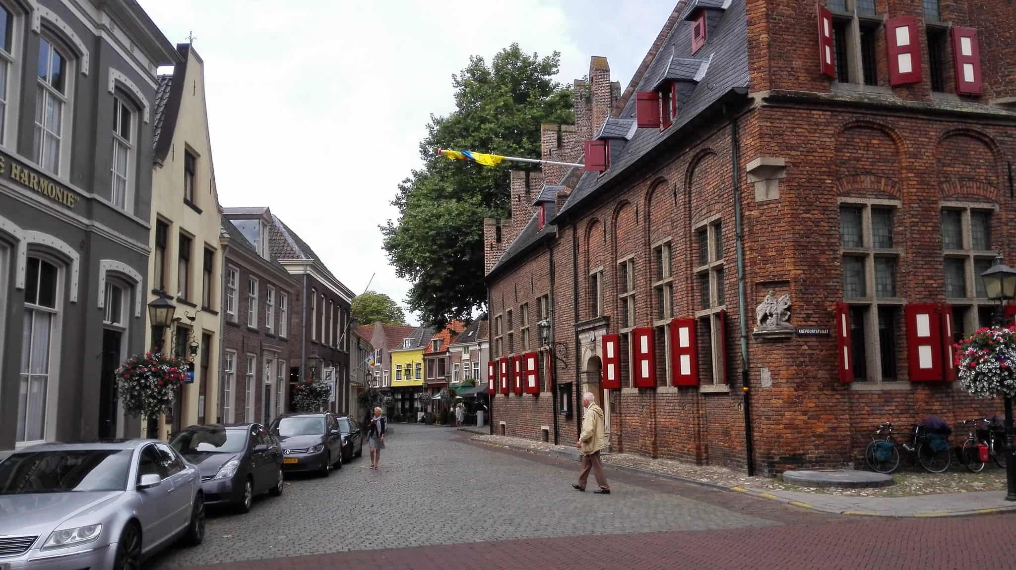 Een man loopt over de straat naast een historisch gebouw in Doesburg.
