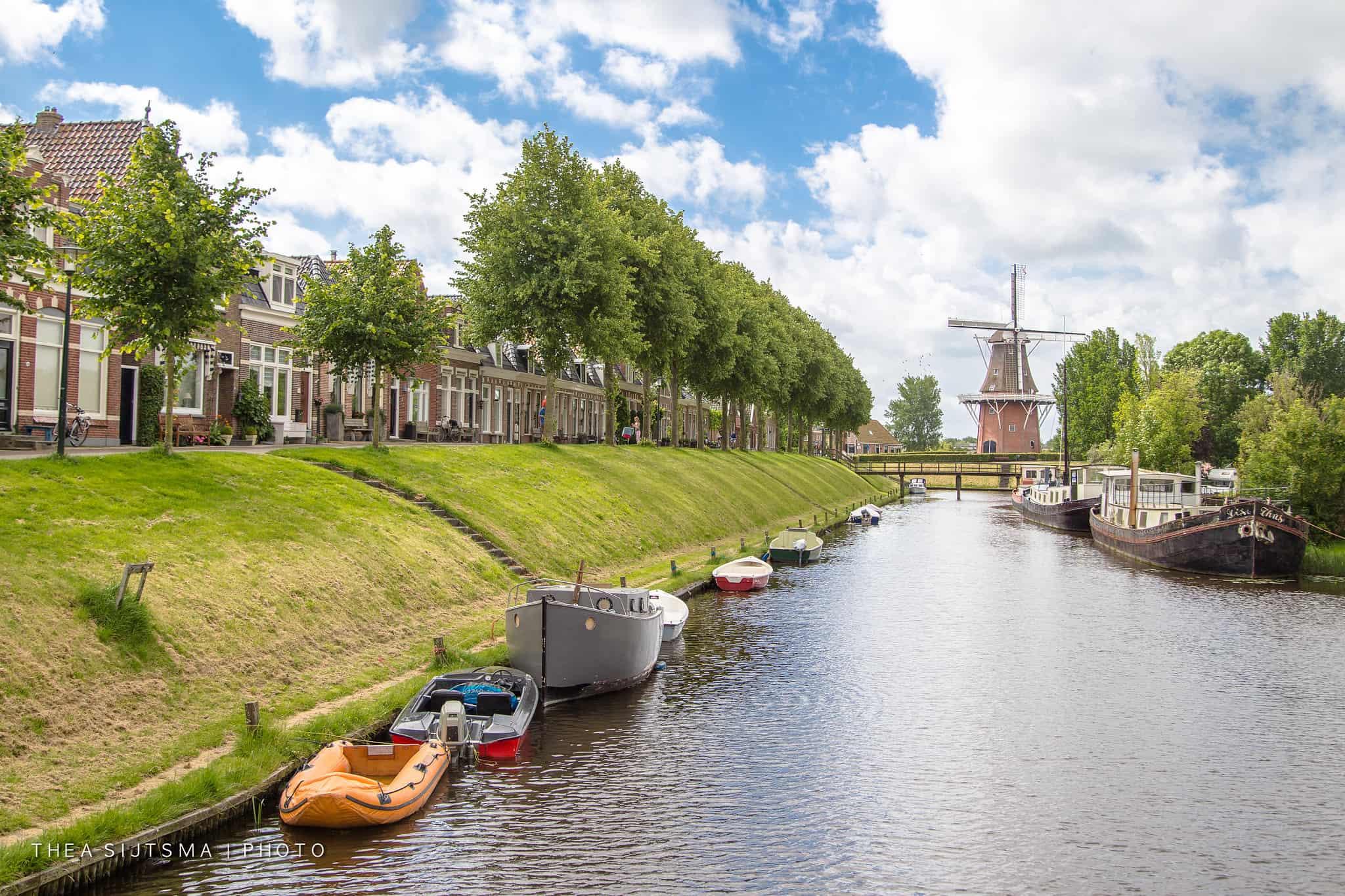 Een rivier geeft op de achtergrond uit op een windmolen in Dokkum, een van de mooiste Nederlandse dorpjes.