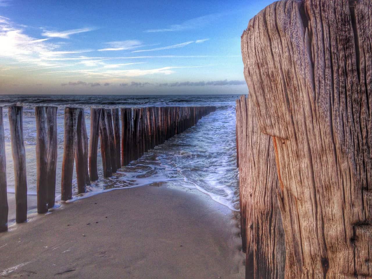 Zeewater spoelt aan op het strand tussen een reeks houten palen.