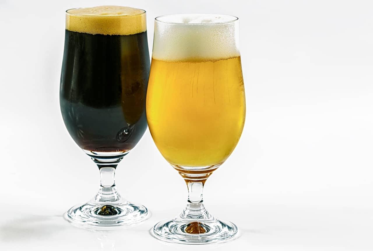 Een glas met donker bier naast een glas met blond bier.