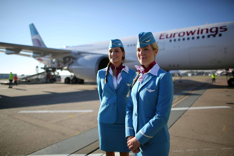 Twee stewardessen staan voor een vliegtuig van Eurowings.
