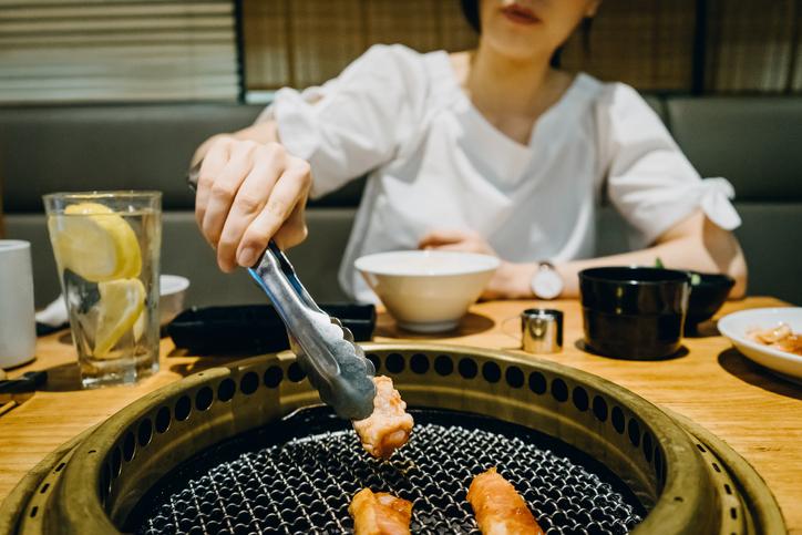 Une femme déguste des substituts de viande dans un restaurant chinois