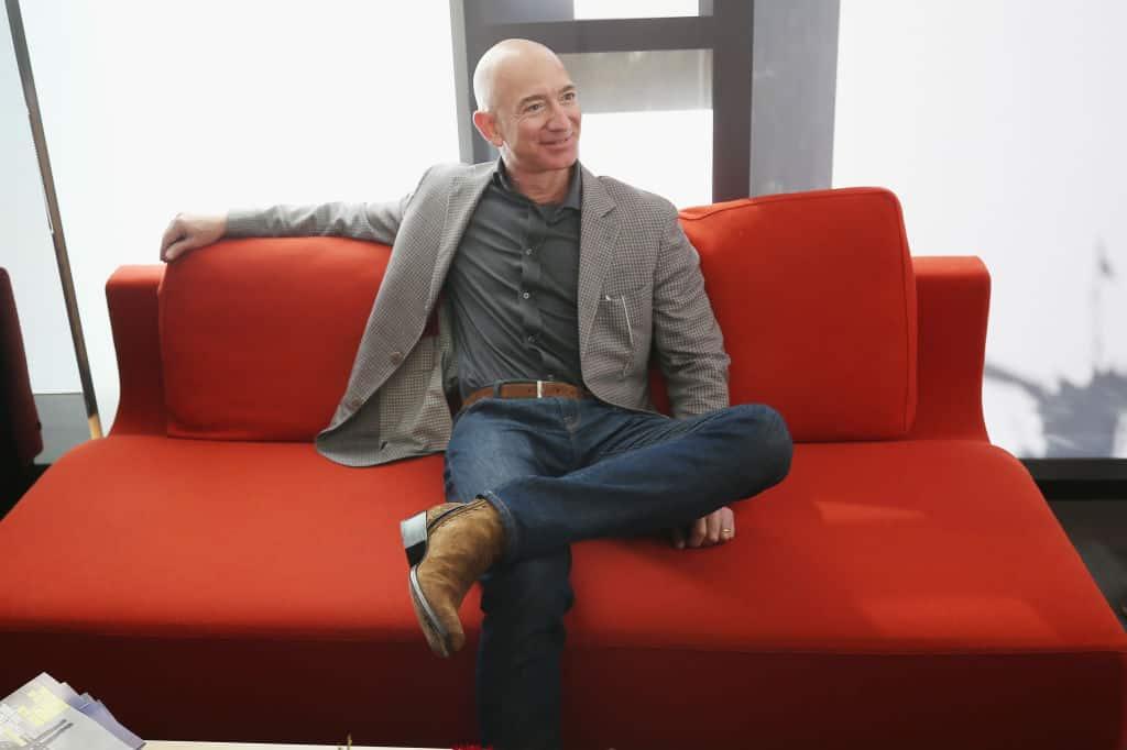 Jeff Bezos zit in kostuum ontspannen met gekruiste benen op een oranje zetel, terwijl hij één arm over de rugleuning legt en glimlacht.