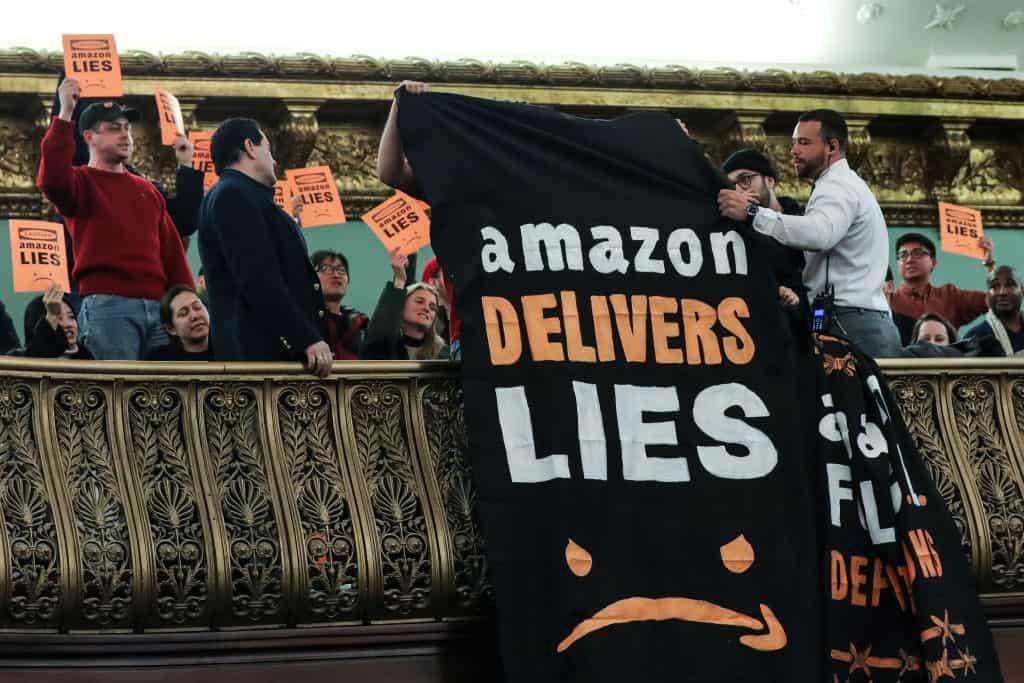 """Medewerkers van Amazon houden een oranje bord vast en laten een doek naar beneden vallen met de tekst: """"Amazon levert leugens."""""""