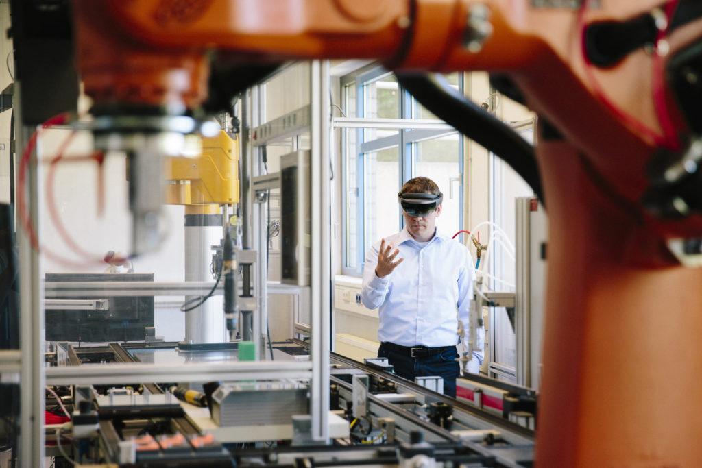 Un ingénieur tente de déplacer un bras robotisé d'une ligne de production grâce à des HoloLens
