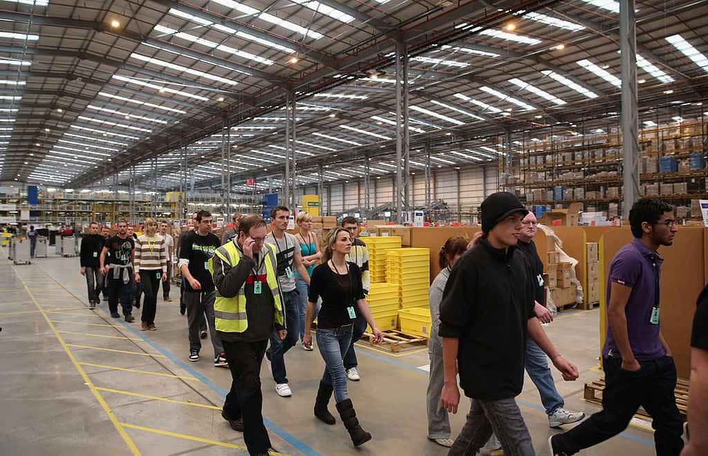 Medewerkers van Amazon lopen door een gangpad in een magazijn.