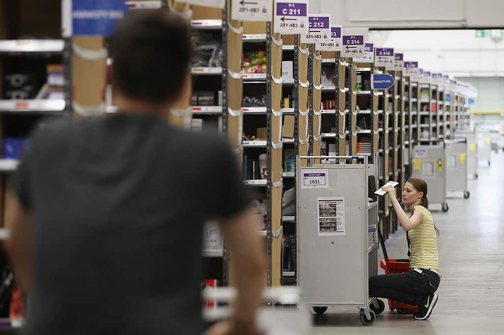De schim van een man in een zwart shirt op de voorgrond, terwijl voor hem een jonge vrouw in een geel shirt op de grond zit aan talrijke gangen met items in een Amazon-magazijn.