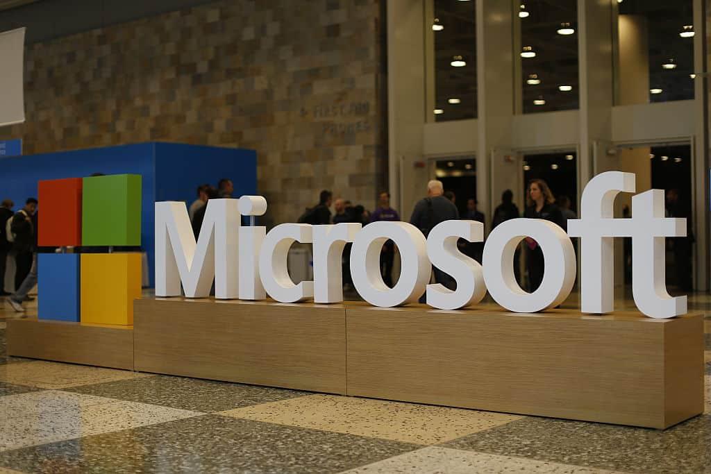 Het logo van Microsoft staat in witte letters op een houten balustrade.