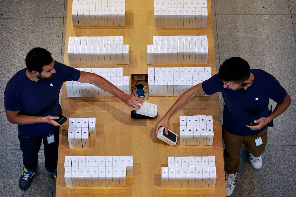 Twee medewerkers van Apple met in het midden een houten tafel vol doosjes met iPhones.