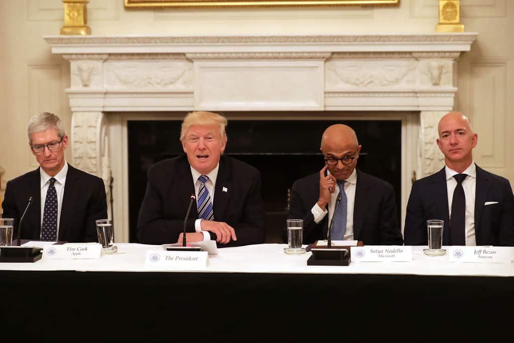 Vier mensen zitten naast elkaar: Donald Trump is de tweede en spreekt, Jeff Bezos is de vierde in de rij en luistert met strak gezicht.
