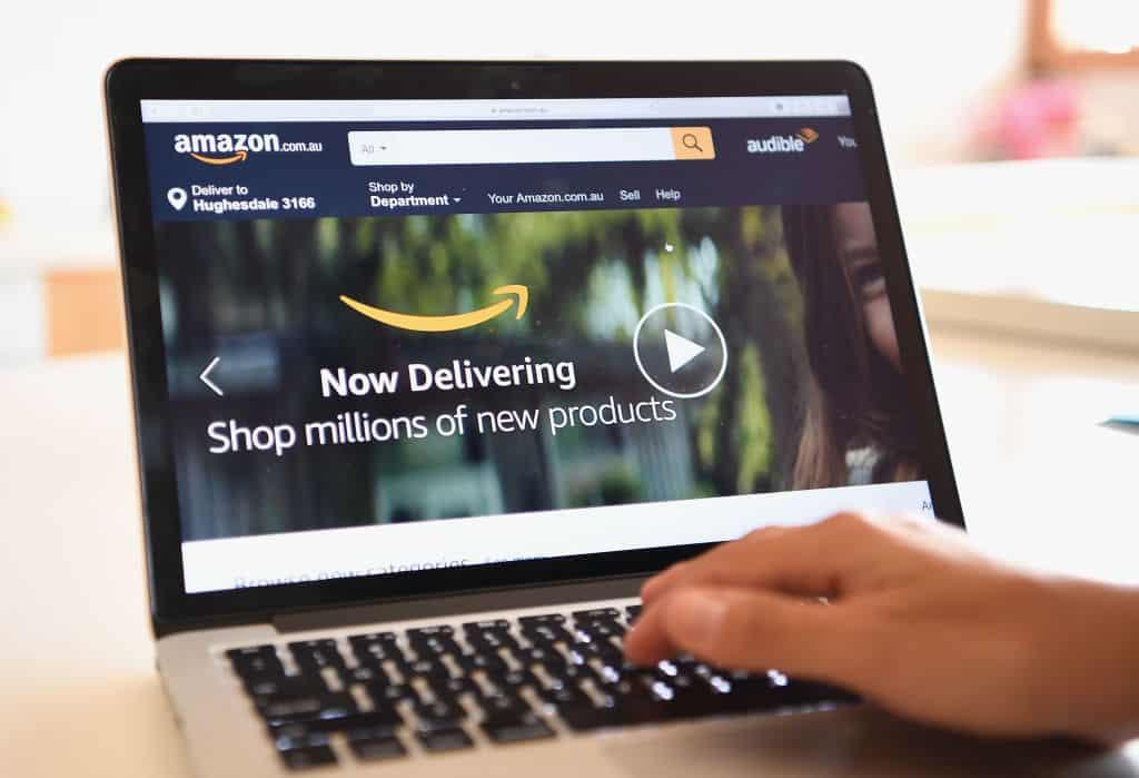 Een hand drukt op een toetsenbord van een laptop met op het scherm de homepagina van Amazon.com.