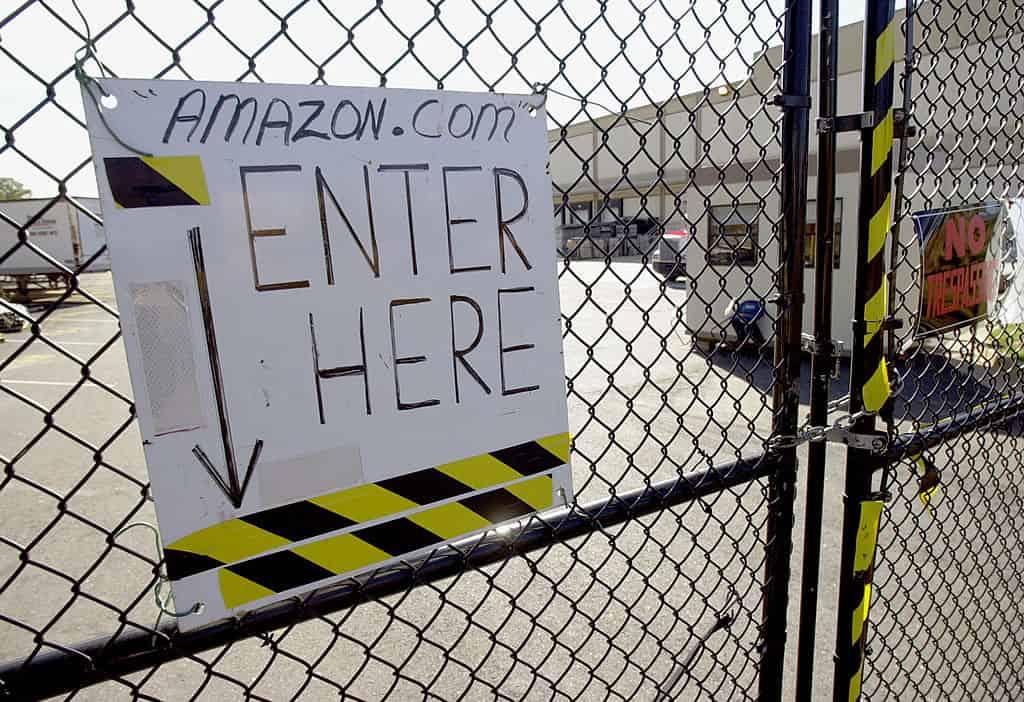 """Een bordje met de tekst """"Amazon.com, kom hier naar binnen"""" hangt aan een hek van een fabriek."""