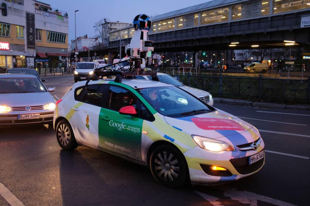 Een auto in verschillende kleuren rijdt met een opvallende camera op het dak. Google maakt op deze manier beelden voor Street View.
