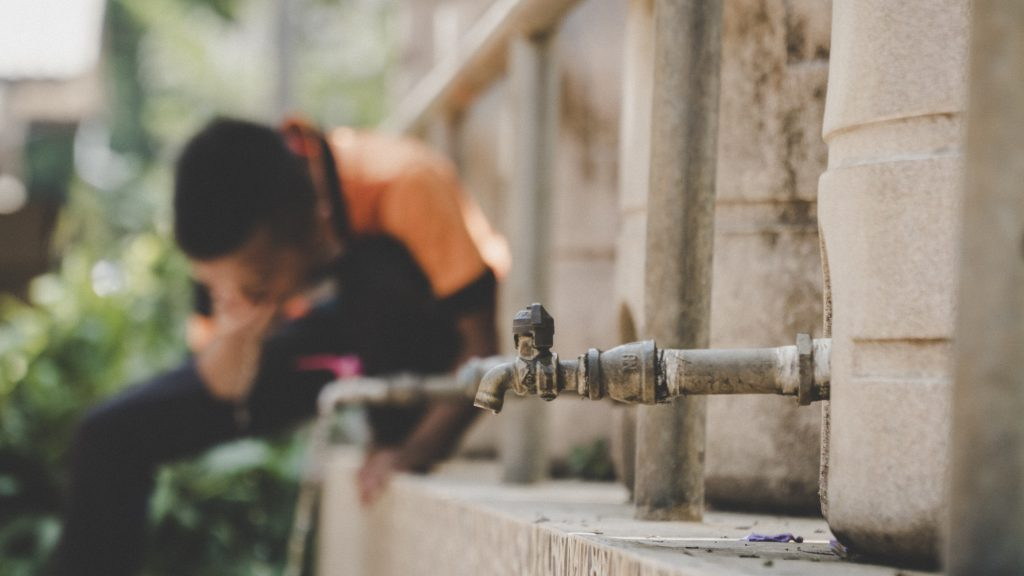 CLOSE-UP OF MAN WORKING AT WATER