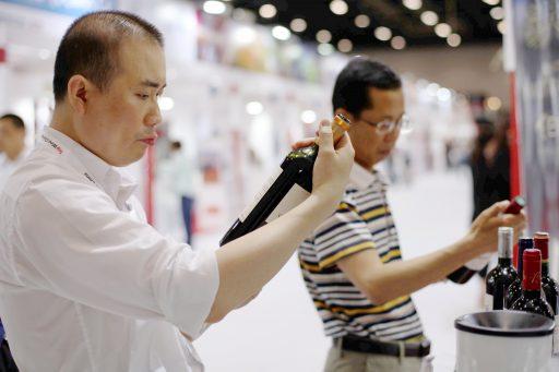 Chinese bezoekers bekijken geïmporteerde wijnen op een wijnevent