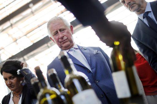 De Britse prins Charles kijkt naar wijnflessen
