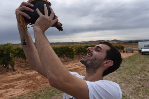 Man drinkt wijn uit een zak na de druivenoogst