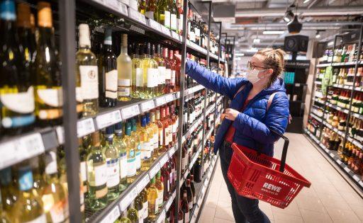 Een vrouw koopt wijn in de winkel