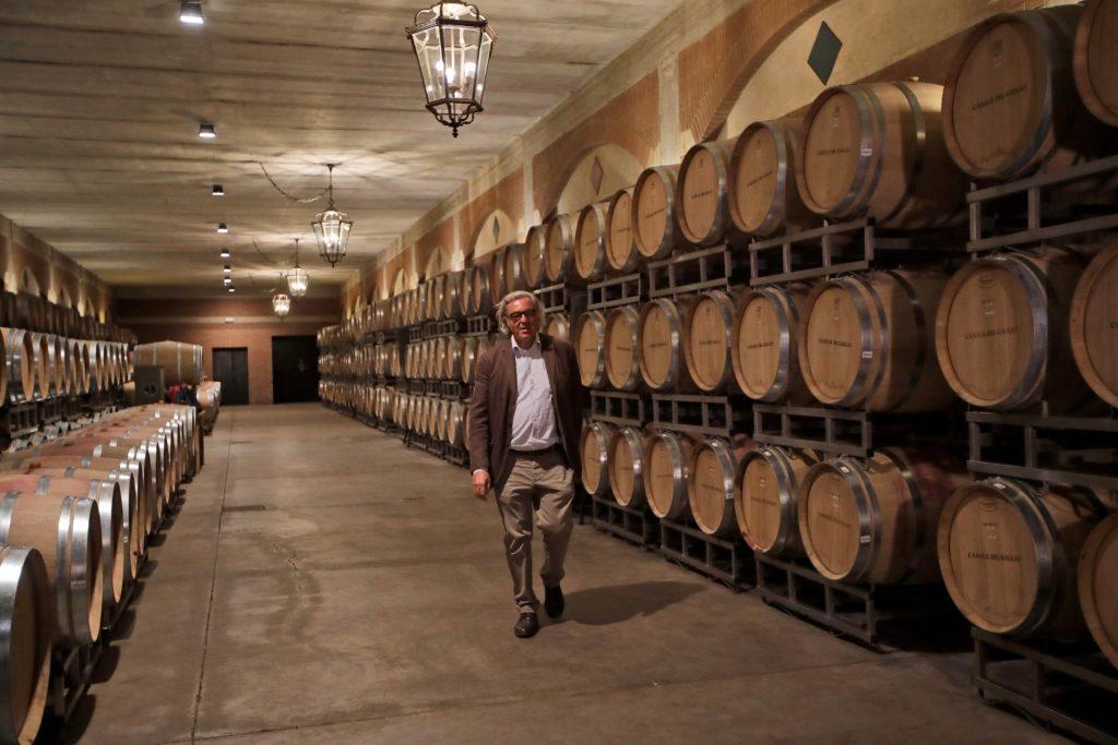 Een Italiaanse wijnmaker loopt in z'n opslagplaats