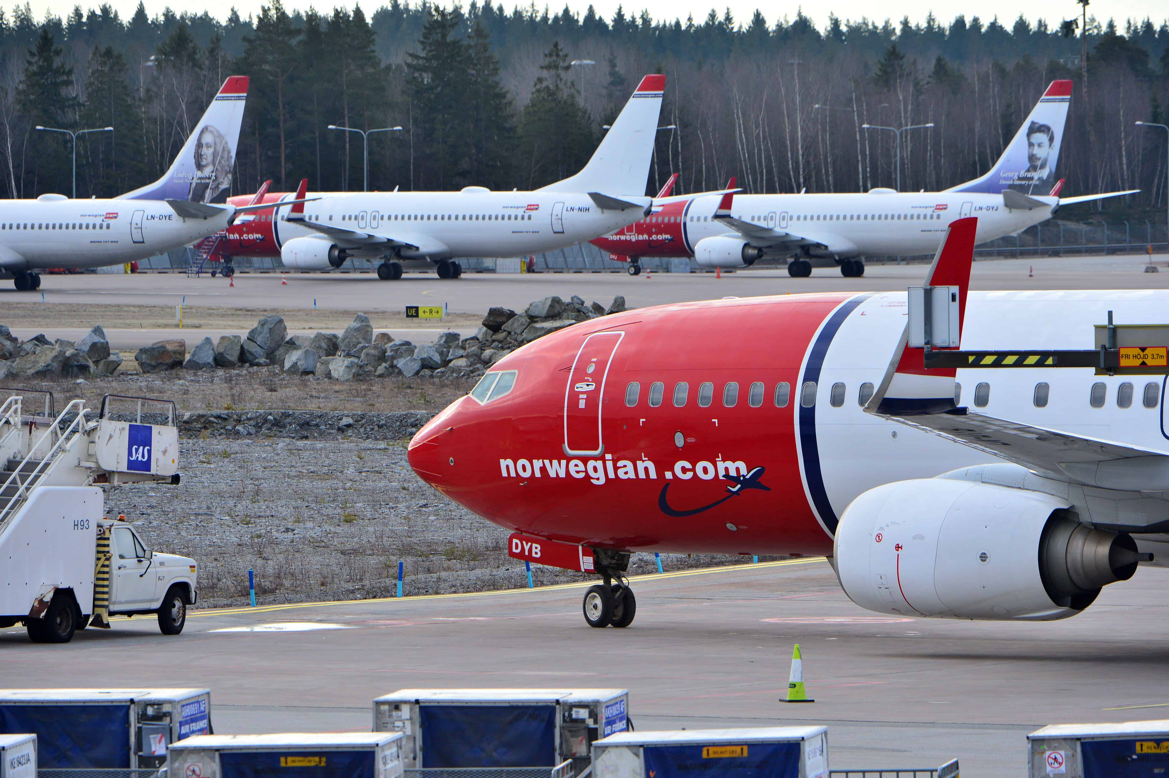 Vliegtuigen van Norwegian staan naast elkaar.