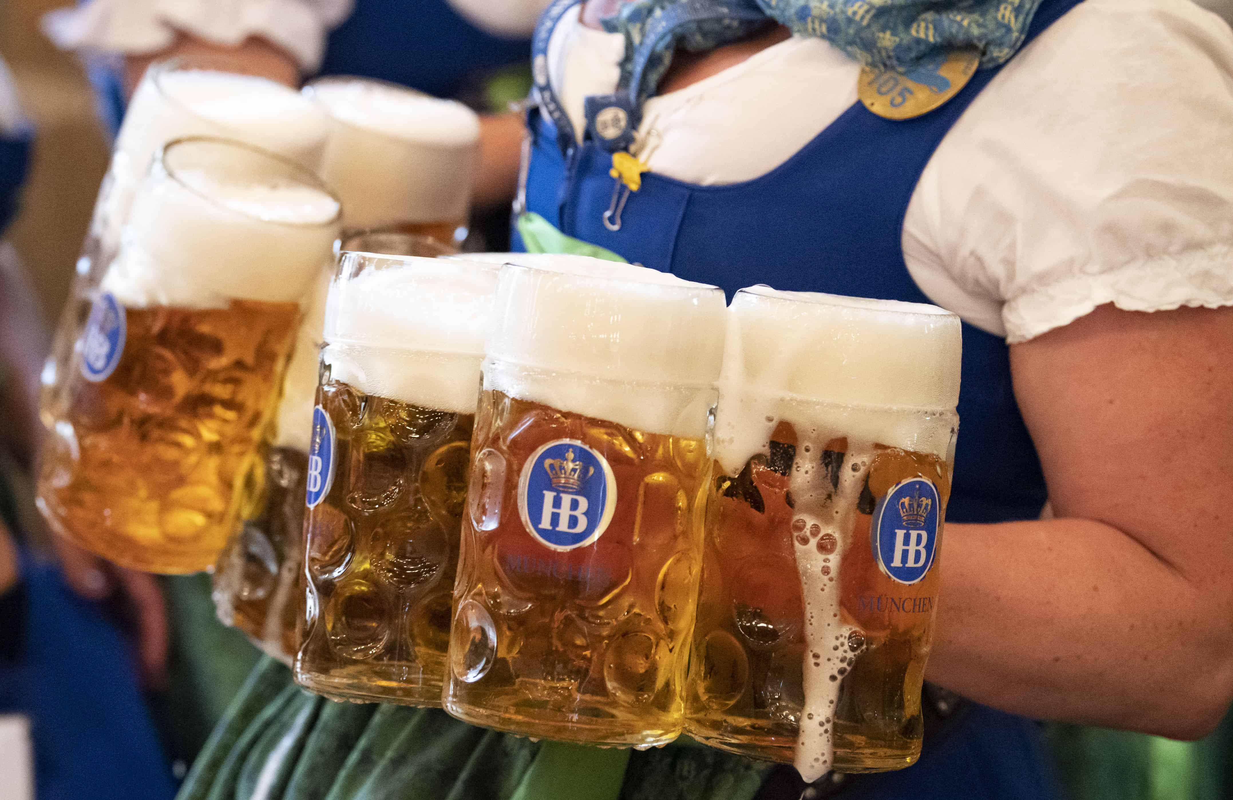 Grote pinten bier worden door een vrouw in Beierse klederdracht aangevoerd.