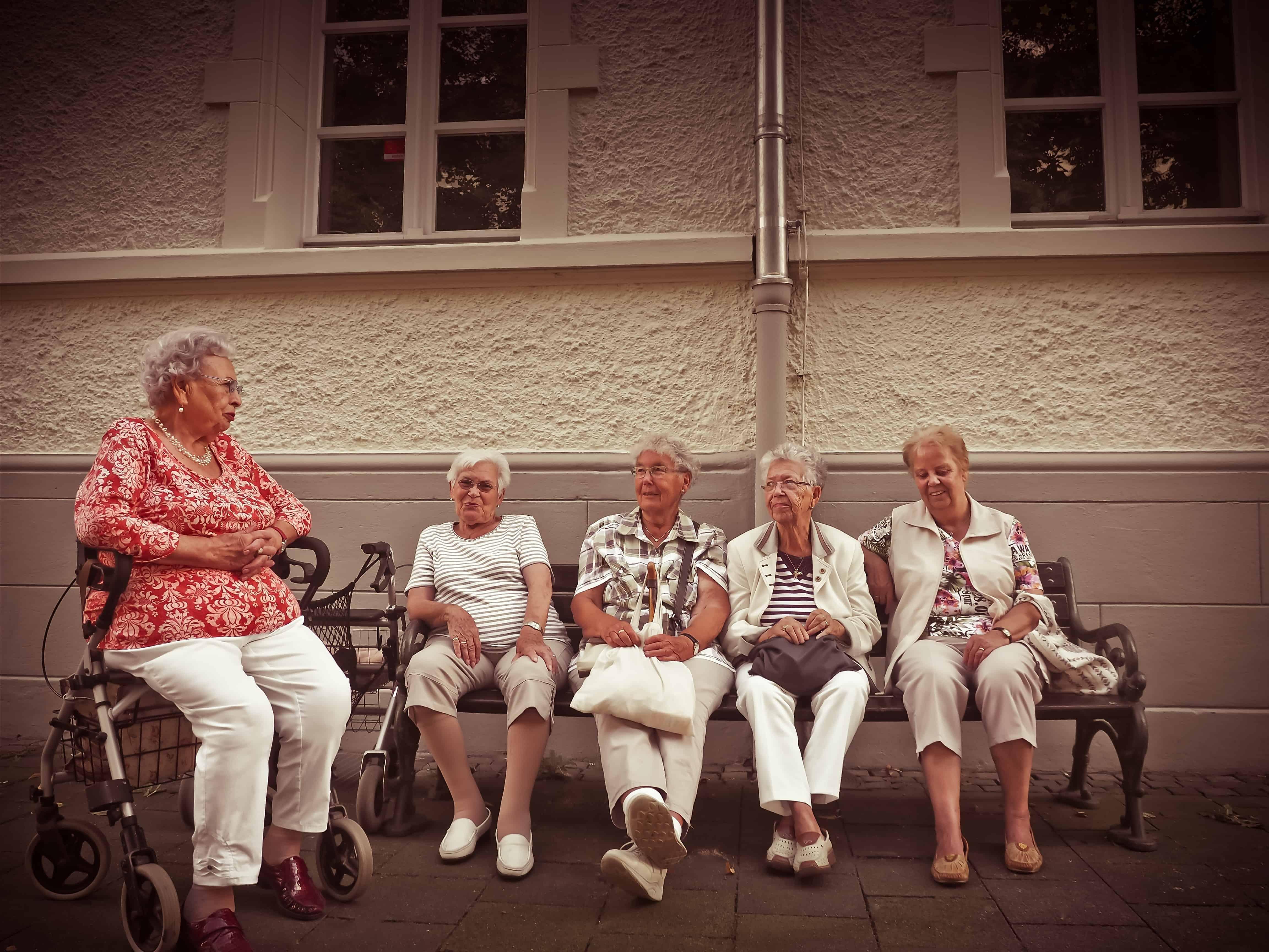 Une vieille femme en fauteuil roulant parle à quatre vieilles femmes assises sur un canapé.