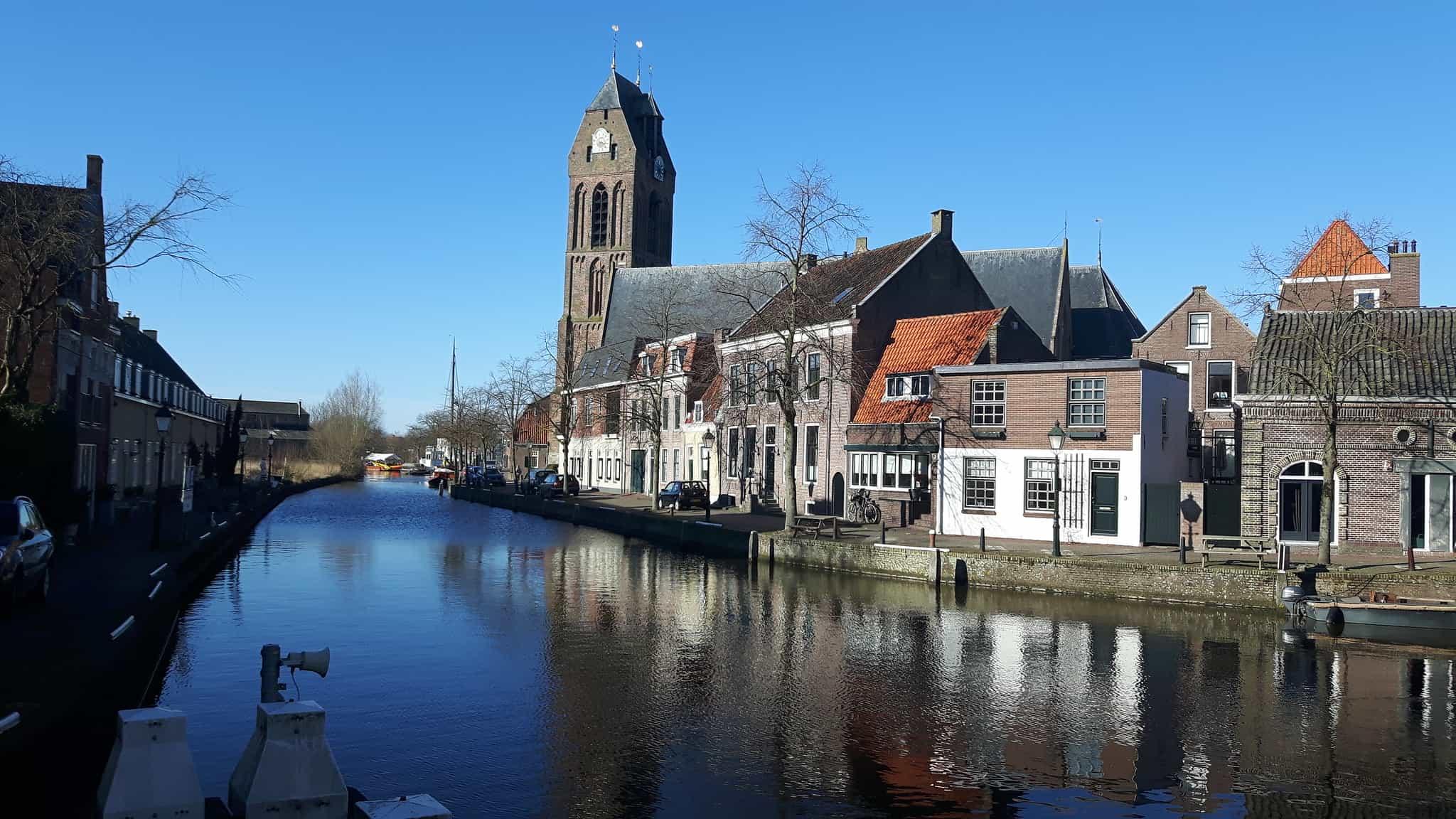 Een kerk en huizen langs een rivier in Oudewater.