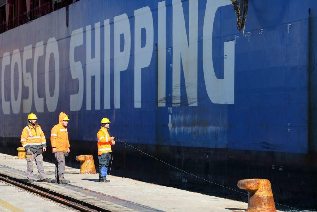 Des dockers déchargent un porte-conteneurs chinois dans le port grec du Pirée. En 2016, l'entreprise publique chinoise COSCO SHIPPING a acheté une participation de 67 % dans le port en difficulté. L'UE veut freiner cette influence croissante de la Chine sur les secteurs clés européens. (Isopix)