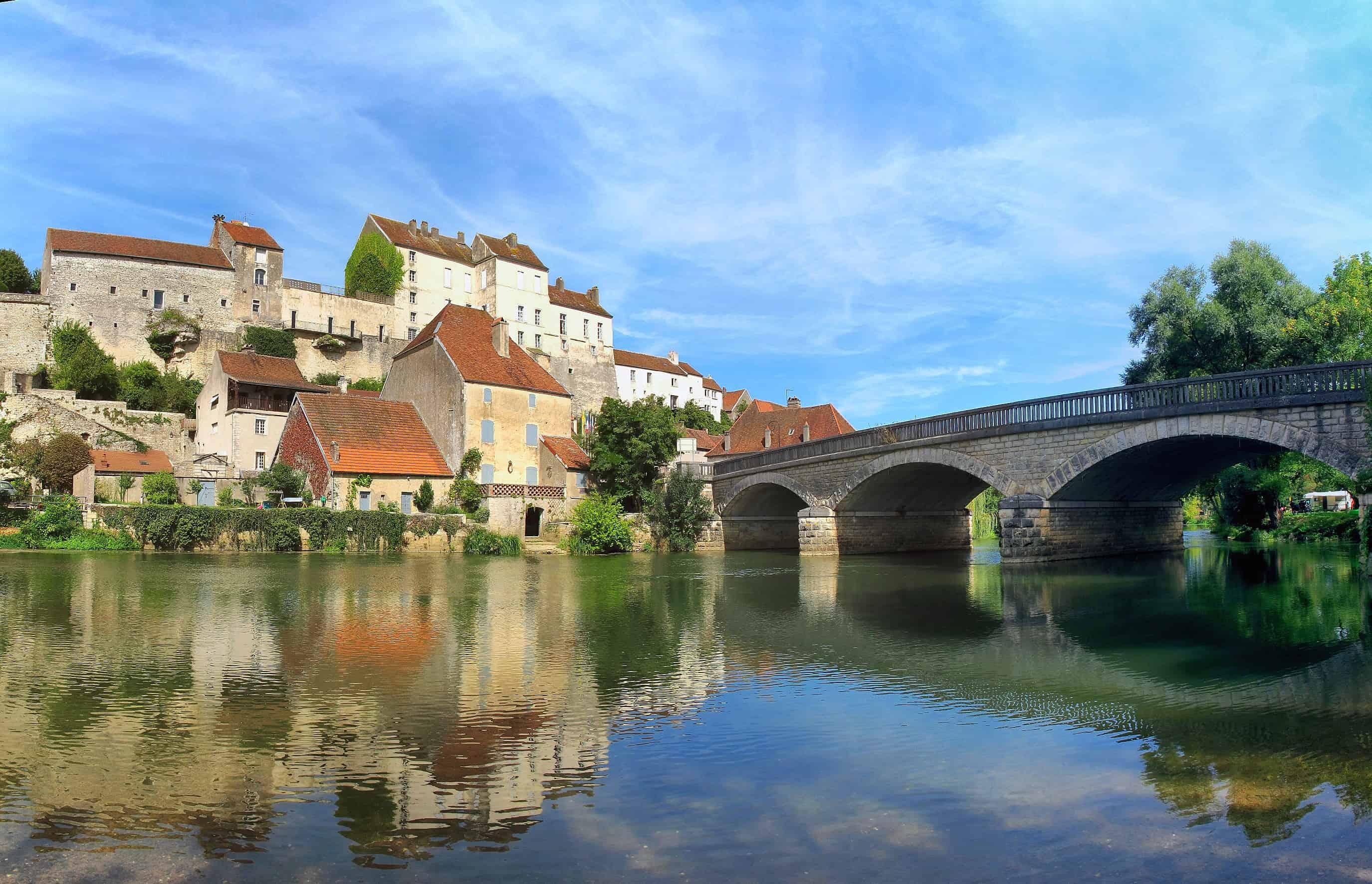 Een brug over het water leidt naar Pesmes, een van de mooiste Franse dorpjes.