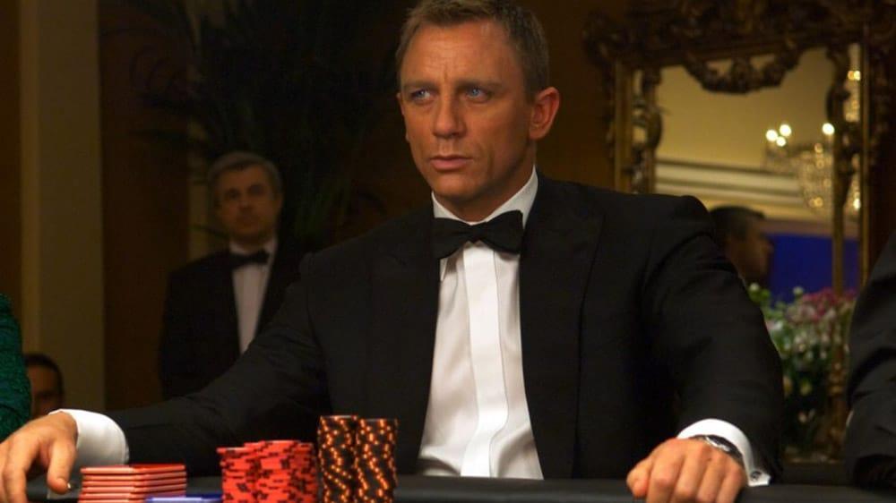 Daniel Craig zit als James Bond aan een pokertafel.