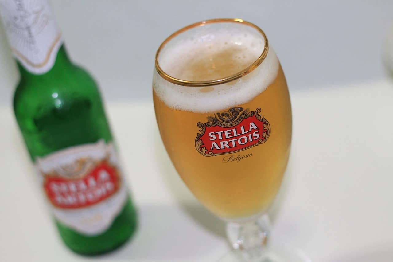 Een groen flesje en een gevuld glas bier met Stella Artois