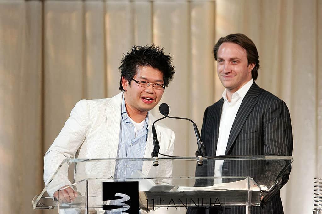 YouTube-oprichter Steve Chen praat in een wit kostuum voor een tafel met microfoon. Achter hem kijkt een man glimlachend toe.