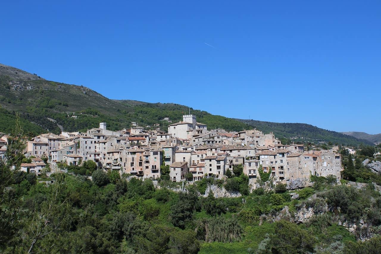 Een beeld van het dorp Tourrettes Sur Loup onder een blauwe hemel.